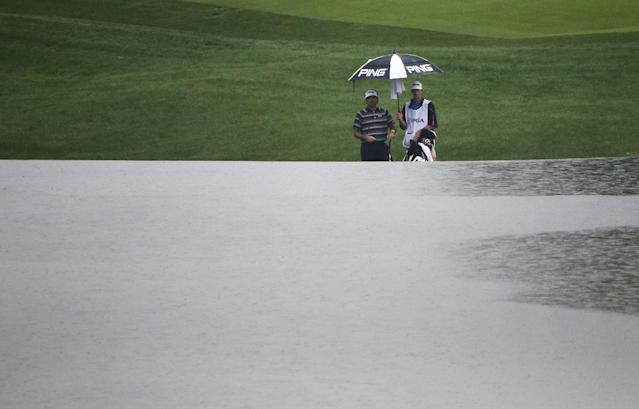 Bubba Watson watches as rain falls on the late along the 18th hole during the second round of the PGA Championship golf tournament at Valhalla Golf Club on Friday, Aug. 8, 2014, in Louisville, Ky. (AP Photo/Mike Groll)