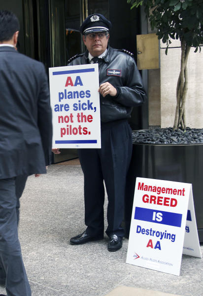American Airlines pilot Sam Mayer pickets in front of a hotel where American Airlines CEO Tom Horton held a meeting with reporters, in New York, Monday, Oct. 8, 2012. In September, American Airlines saw a 7.1 percent drop in domestic passengers and its on-time performance fell to 59 percent, below other big airlines. The drop is attributed to pilots who are writing up extra maintenance requests as part of an unsanctioned job action. If that wasn't bad enough, seats on three separate flights came loose. (AP Photo/Seth Wenig)