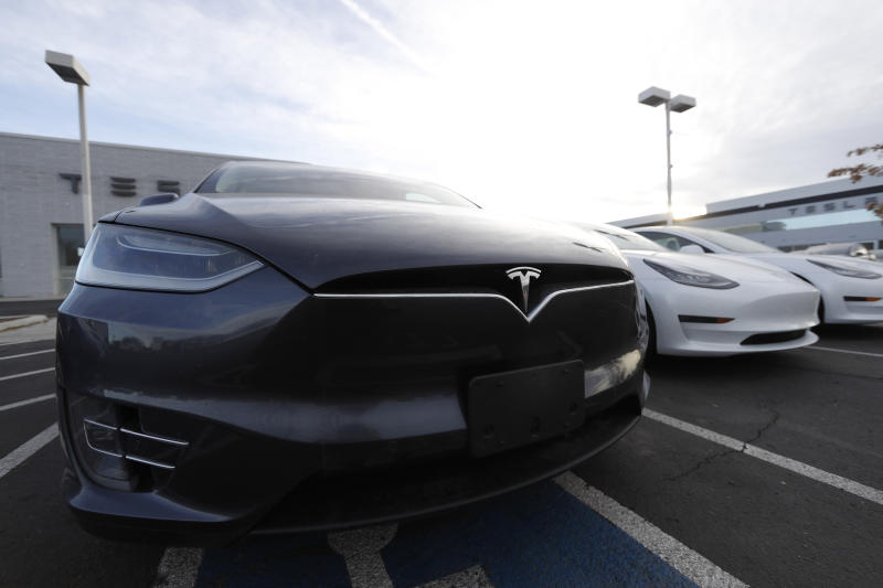FILE - In this Nov. 10, 2019, file photo an unsold Model X sports-utility vehicle sits with other vehicles at a Tesla dealership in Littleton, Colo. Shares of Tesla Inc. continued their wild run Wednesday, Jan. 22, 2020, rising another 6.3% and pushing the electric car and solar panel maker's market value above $100 billion. (AP Photo/David Zalubowski, File)