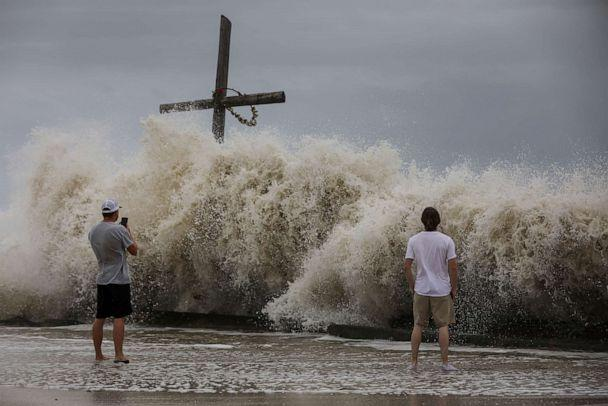 PHOTO: Mark Allums, left, and Hunter Clark watch waves crash ashore as outer bands from Hurricane Laura begin to hit the coast, Aug. 26, 2020, in High Island, Texas. (Jon Shapley/AP)