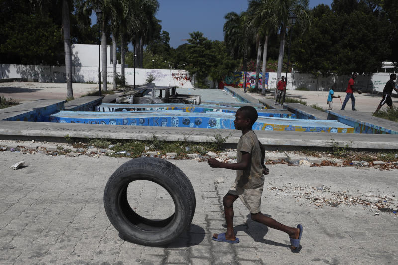 A boy rolls a tire through the Champ de Mars park as protesters prepare to set tires alight in front of the entrance to the National Palace, in Port-au-Prince, Haiti, Monday, Oct. 14, 2019. Haiti's embattled president faced a fifth week of protests on Monday as road blocks went up across the country after opposition leaders said they will not back down on their call for Jovenel Moïse to resign.(AP Photo/Rebecca Blackwell)