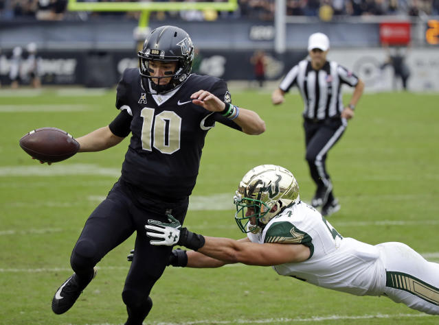 "Central Florida quarterback <a class=""link rapid-noclick-resp"" href=""/ncaaf/players/270182/"" data-ylk=""slk:McKenzie Milton"">McKenzie Milton</a> (10) runs for a 3-yard touchdown past South Florida linebacker Nico Sawtelle during the first half of an NCAA college football game, Friday, Nov. 24, 2017, in Orlando, Fla. (AP Photo/John Raoux)"