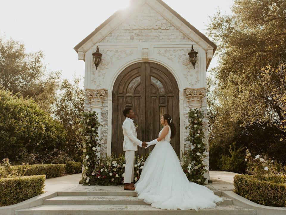 A bride and groom hold hands in front of a chapel.
