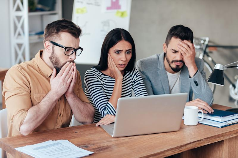 Three people looking at a computer screen and acting concerned