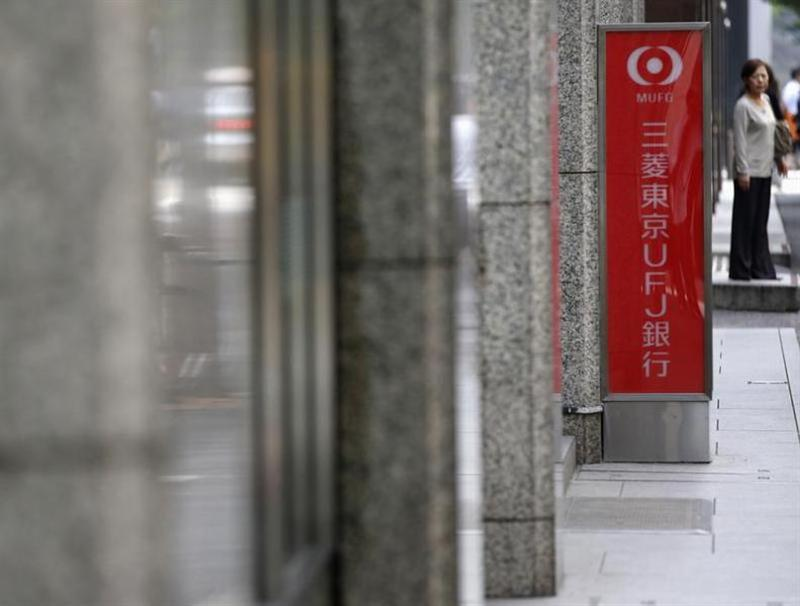 A woman stands near signboard of branch bank of Mitsubishi UFJ Financial Group in Tokyo