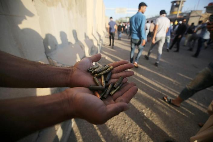 "A supporter of Iraqi cleric Moqtada al-Sadr carries bullet casings following clashes with security forces after they broke into Baghdad's fortified ""Green Zone"" on May 20, 2016 (AFP Photo/Ahmad al-Rubaye)"