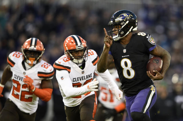 Baltimore Ravens quarterback Lamar Jackson, right, rushes for a touchdown past Cleveland Browns free safety Jabrill Peppers, back left, and strong safety Damarious Randall in the first half of an NFL football game, Sunday, Dec. 30, 2018, in Baltimore. (AP Photo/Gail Burton)