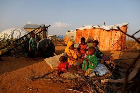 Zeinab's sister Habiba, 29, sits with her children beside their shelter at a camp for internally displaced people from drought hit areas in Dollow, Somalia April 2, 2017. REUTERS/Zohra Bensemra