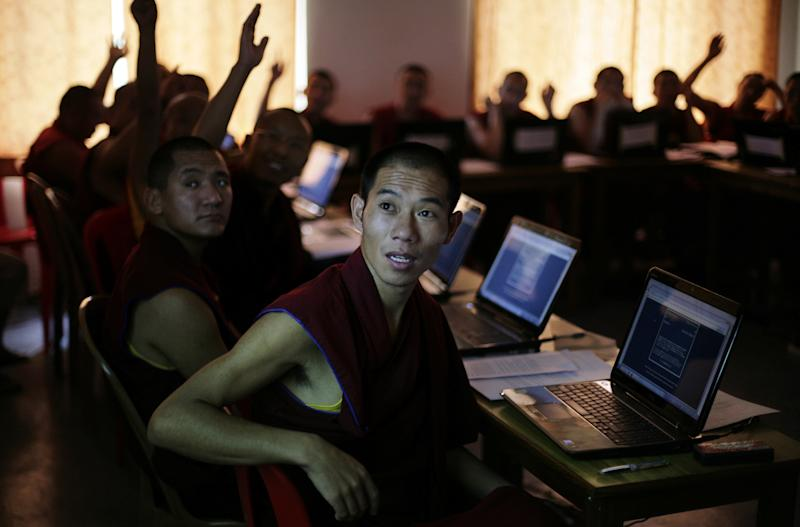 In this June 7, 2012 photo, Tibetan Buddhist monks look at questions displayed on a projector screen during their class at an educational complex in Sarah, India. In the facility perched on the edge of a small river valley, in a place where the Himalayan foothills descend into the Indian plains, this group of Tibetan monks are working with American scientists to tie their ancient culture to the modern world. (AP Photo/Altaf Qadri)