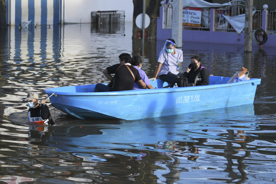 A Thai volunteer man pulls a boat carrying evacuees in a flooded area in Chaiyaphum province, northeast of Bangkok, Thailand, Tuesday, Sept. 28, 2021. Thai disaster officials say flooding caused by seasonal monsoon rains have affected more than 71,000 households in 30 provinces and killed six people since the weekend. (AP Photo/Thanachote Thanawikran)