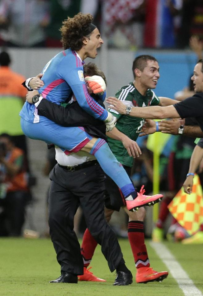 Mexico's goalkeeper Guillermo Ochoa celebrates with head coach Miguel Herrera celebrates after Mexico's Andres Guardado  scored his side's second goal during the group A World Cup soccer match between Croatia and Mexico at the Arena Pernambuco in Recife, Brazil, Monday, June 23, 2014.   (AP Photo/Petr David Josek)