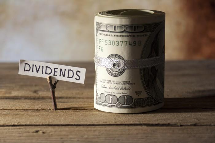 A roll of hundred-dollar bills next to a sign that reads DIVIDENDS.