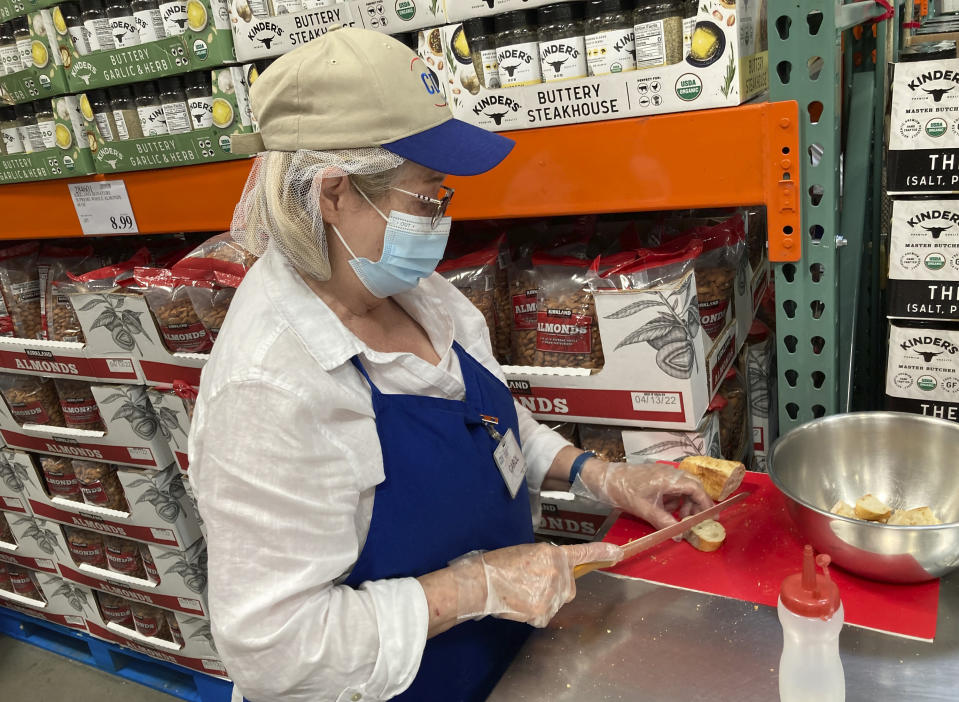 A worker prepares bread to offer as samples to shoppers in a Costco warehouse on Thursday, June 17, 2021, in Lone Tree, Colo. With vaccinations rolling out and the threat of COVID-19 easing in the U.S., stores are feeling confident enough to revive the longstanding tradition of offering free samples. For customers, sampling makes it fun to shop and discover new items, not to mention getting all the freebies. (AP Photo/David Zalubowski)
