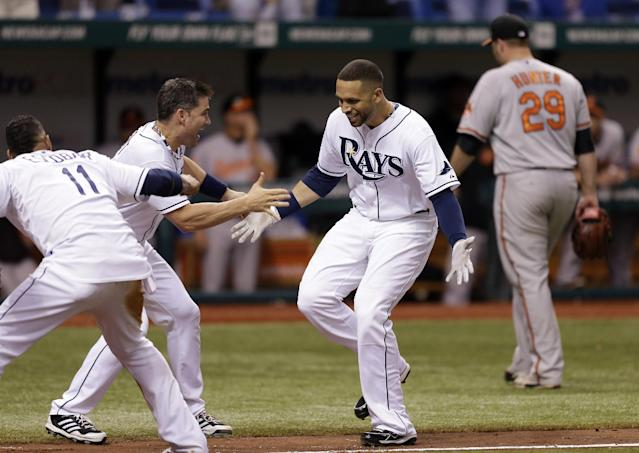 Tampa Bay Rays' James Loney, second from right, greets teammates Yunel Escobar, left, and Luke Scott, second from left, after hitting a ninth-inning, game-winning home run off Baltimore Orioles relief pitcher Tommy Hunter, right rear, during a baseball game Monday, Sept. 23, 2013, in St. Petersburg, Fla. The Rays won 5-4. (AP Photo/Chris O'Meara)