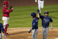 Tampa Bay Rays' Brandon Lowe, right, is congratulated by Brett Phillips, center, after hitting a three-run home run as Los Angeles Angels catcher Kurt Suzuki stands behind the plate during the seventh inning of a baseball game Wednesday, May 5, 2021, in Anaheim, Calif. (AP Photo/Mark J. Terrill)
