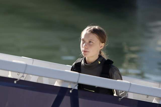 Climate activist Greta Thunberg walks on a gangway to the quay in Lisbon