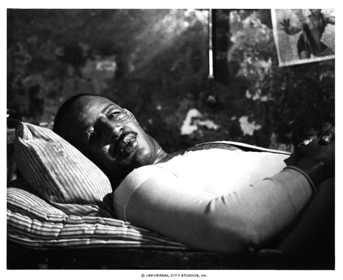 Frank McRae laying in bed in a scene from the film 'Paradise Alley', 1978. (Photo by Universal/Getty Images)