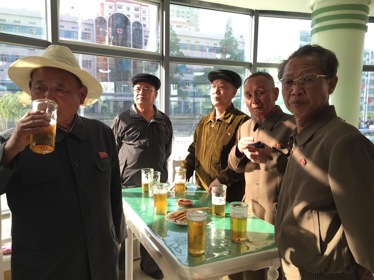 In this May 7, 2016 photo, men, wearing loyalty pins bearing portraits of former leaders Kim Il Sung or Kim Jong Il, or both, take a break in a beer hall in Pyongyang, North Korea. Wearing the pins above the heart is mandatory for all adults in North Korea. (AP Photo/Eric Talmadge)