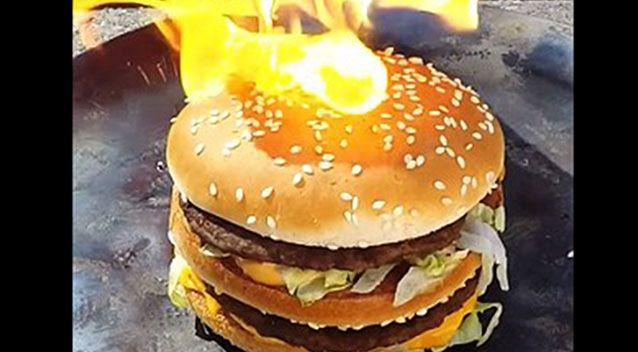 The burger first burst into flames but then the buns appeared to act as a 'flame-retardant. Source: YouTube.