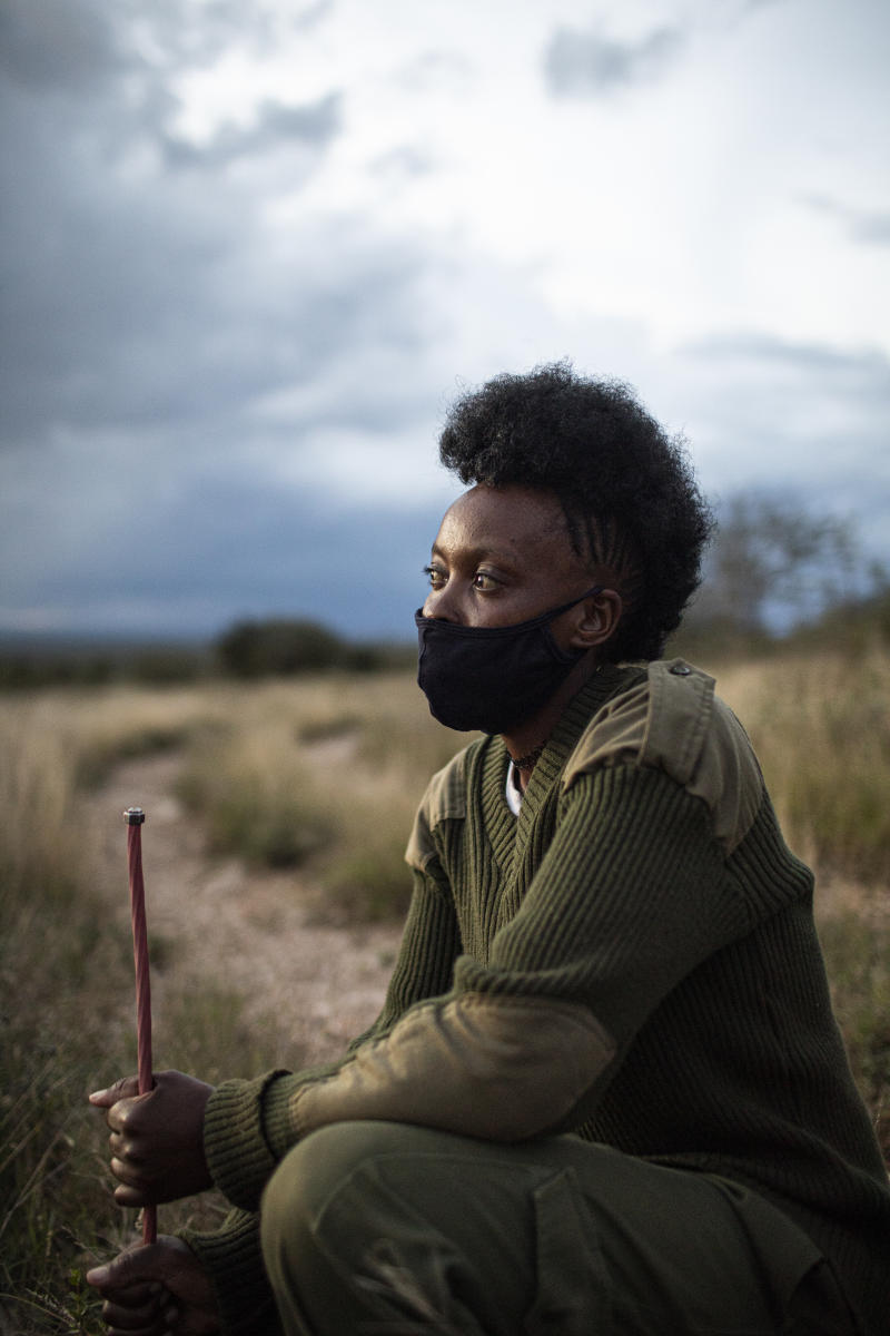 Ranger Beatrice Sailepu wears a face mask and green fatigues. She swats on the ground, holding a stick.