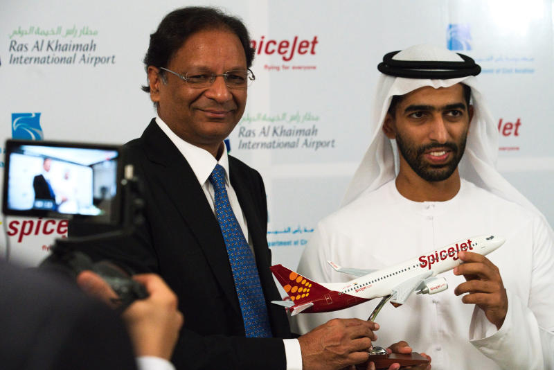 SpiceJet chairman and managing director Ajay Singh, left, and Sheikh Khalid bin Saud Al Qasimi, a son of Ras al-Khaimah ruler Sheikh Saud bin Saqr Al Qasimi, right, pose for photographs during a news conference in Ras al-Khaimah, United Arab Emirates, Wednesday, Oct. 23, 2019. India's low-cost airline SpiceJet announced plans Wednesday to build its first international hub in the United Arab Emirates, offering a pledge of support to Boeing Co. by saying it would use now-grounded 737 MAX aircraft in the operation once regulators approve the planes for flight. (AP Photo/Jon Gambrell)