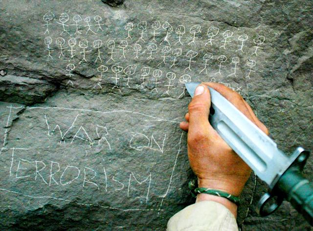<p>United States Army 10th Mountain Division soldier Jorge Avino from Miami, Florida carves the body count that their mortar team has chalked up on a rock, March 9, 2002 near the villages of Sherkhankheyl, Marzak and Bobelkiel, in Afghanistan. (Photo: Joe Raedle/Reuters) </p>