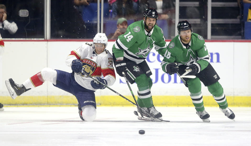 Florida Panthers' Dryden Hunt battles over the puck with Dallas Stars' Jamie Benn (14) and Joe Pavelski durding the first period of a preseason NHL hockey game in Tulsa, Okla., Saturday, Sept. 21. 2019. (AP Photo/Dave Crenshaw)