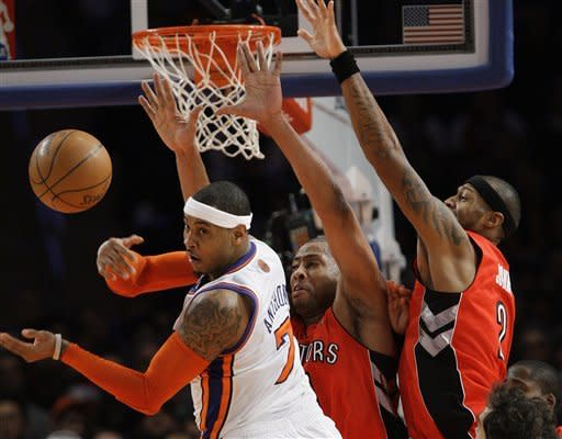 New York Knicks' Carmelo Anthony (7) passes away from Toronto Raptors' Jamaal Magloire, center, and James Johnson (2) during the second half of an NBA basketball game Monday, Jan. 2, 2012, in New York. The Knicks lost the game 90-85. (AP Photo/Frank Franklin II)