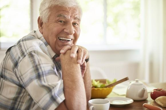 Smiling senior man seated at a kitchen table, hands folded under his chin, with food and dishes on the table in front of him.