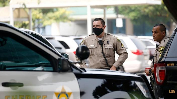 Los Angeles County Sheriffs Department (LASD) deputies stand outside St Francis Medical Center hospital following the ambush shooting