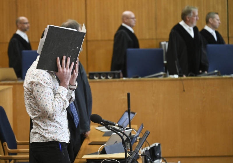 At the opening of the trial, the defendant covers his face with a folder as he stands near his chair in the courtroom while the presiding judge Thomas Sagebiel (second from right) arrives at the Higher Regional Court (OLG) in Frankfurt, Germany, Friday, April 24, 2020. The 37-year-old Iraqi defendant on suspicion of the murder of a five-year-old girl in Syria . The Federal Prosecutor's Office also charges him with genocide, membership of a terrorist organisation and human trafficking. (Arne Dedert/Pool via AP)