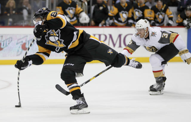 Pittsburgh Penguins' Phil Kessel, left, snaps a shot as Vegas Golden Knights' Colin Miller (6) defends during the second period of an NHL hockey game Thursday, Oct. 11, 2018, in Pittsburgh. Kessel scored on the play, his second of the period and third of the game. (AP Photo/Keith Srakocic)