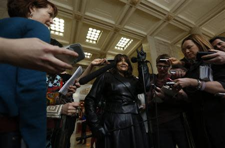 Bedford, one of three current and former sex workers who initiated a challenge to Canada's prostitution laws, flashes a victory sign while speaking with journalists at the Supreme Court of Canada in Ottawa