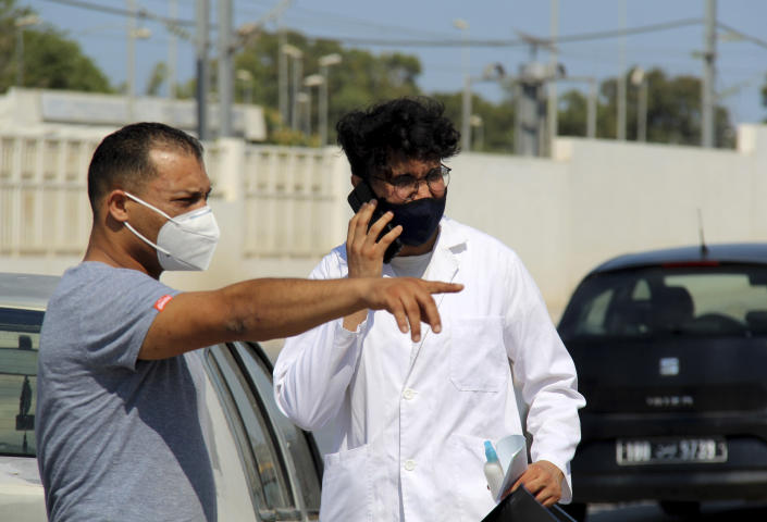 People wearing face masks to protect from COVID-19, stand outside a hospital in Tunis, Tunisia, Wednesday, July 21, 2021. Tunisia's president on Wednesday ordered the military to take over management of the national COVID-19 pandemic response, as the country fights one of Africa's worst outbreaks. (AP Photo/Hassene Dridi)