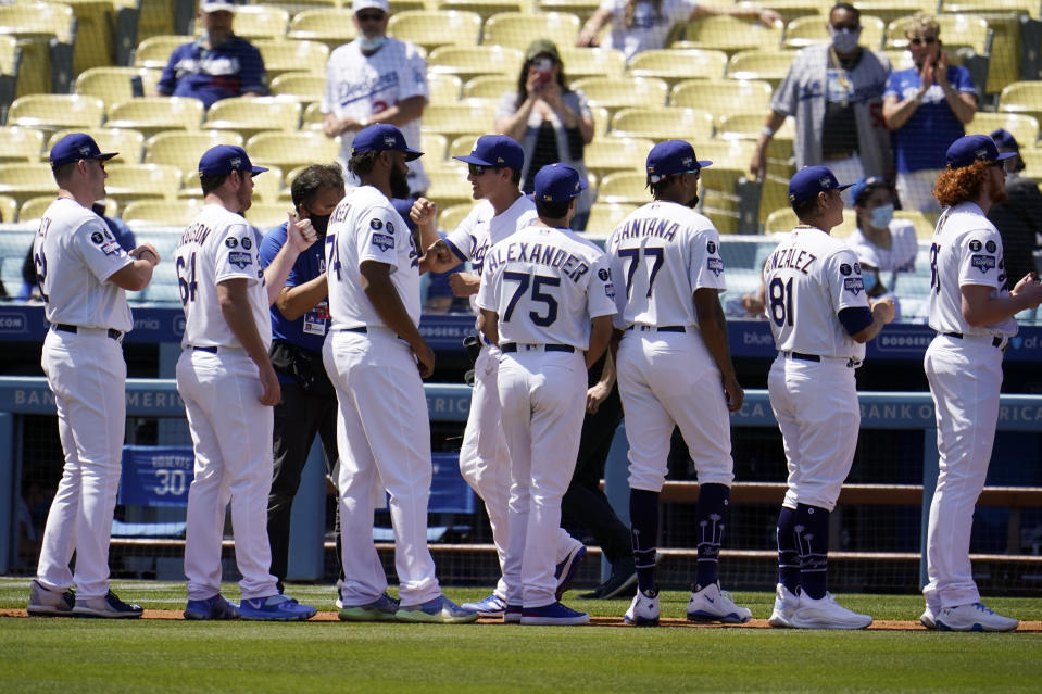Members of the Los Angeles Dodgers greet each other during player introductions before a baseball game against the Washington Nationals, Friday, April 9, 2021, in Los Angeles. (AP Photo/Marcio Jose Sanchez)