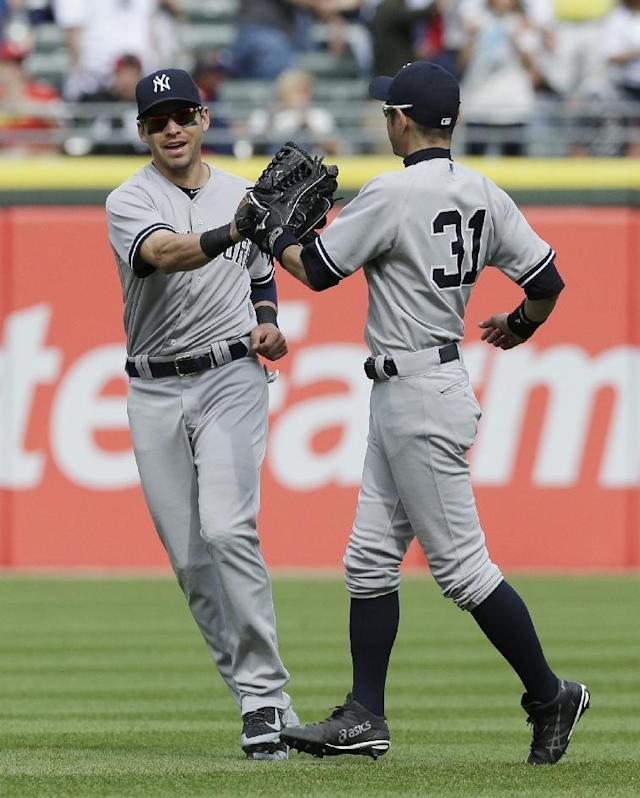 New York Yankees center fielder Jacoby Ellsbury, left, celebrates with right fielder Ichiro Suzuki, of Japan, after the Yankees defeated the Chicago White Sox 4-3 in a baseball game in Chicago on Saturday, May 24, 2014. (AP Photo/Nam Y. Huh)