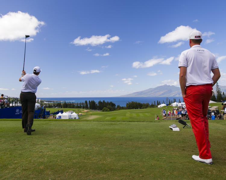 As Webb Simpson watches, right, Michael Thompson drives off the first tee during the third round of the Tournament of Champions golf tournament, Sunday, Jan. 5, 2014, in Kapalua, Hawaii. (AP Photo/Marco Garcia)