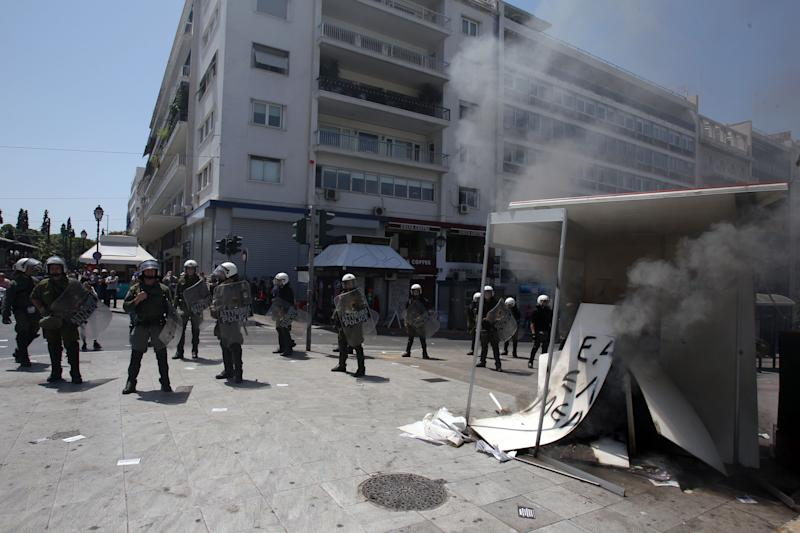 Riot police stand next to a burning election kiosk of an independent right-wing candidate by protesters during a May Day protest in Athens, Tuesday, May 1, 2012. In debt-crippled Greece, more than 2,000 people marched through central Athens in subdued May Day protests centered on the country's harsh austerity program. The Greek elections are scheduled for Sunday, May 6. (AP Photo/Thanassis Stavrakis)