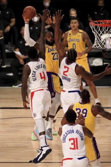 Lakers forward LeBron James is defended by the Clippers' JaMychal Green (4) and Kawhi Leonard (2) during the fourth quarter.