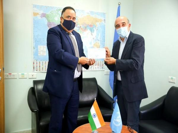 India's representative to Palestine, Sunil Kumar (L) handing over the check for UN Relief and Works Agency for Palestine Refugees in Near East (UNRWA).