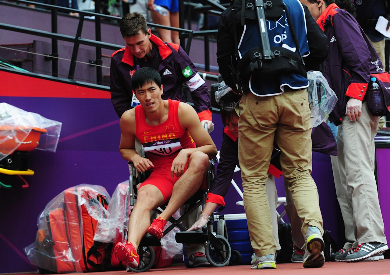 Xiang Liu of China gets assisted off the track after getting injured in the Men's 110m Hurdles Round 1 Heats on Day 11 of the London 2012 Olympic Games at Olympic Stadium on August 7, 2012 in London, England.  (Photo by Stu Forster/Getty Images)