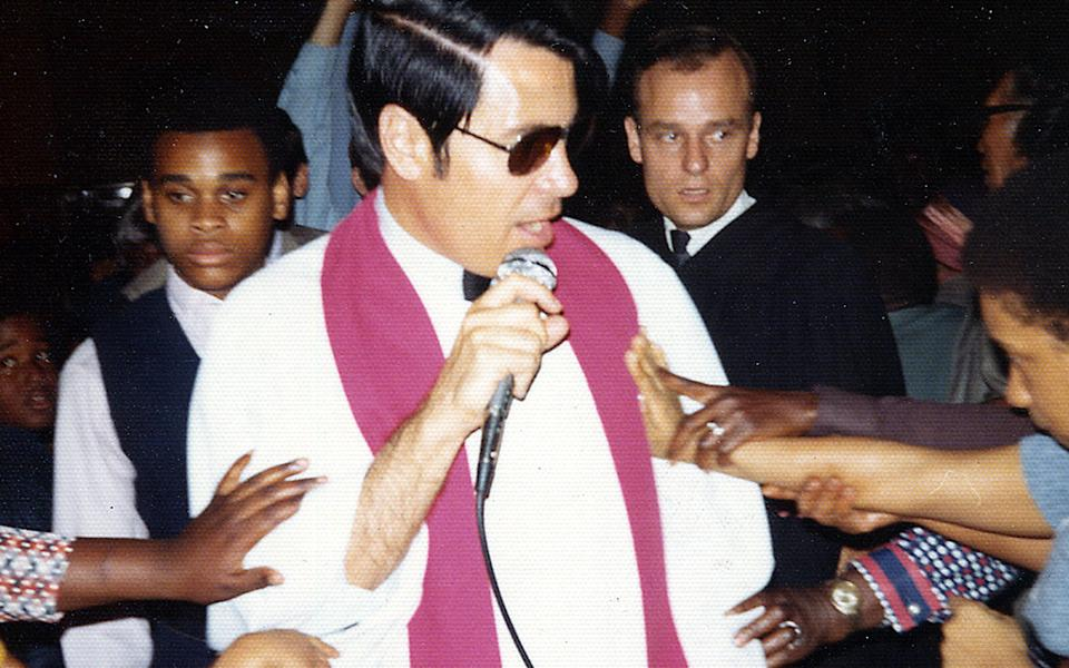 Followers reach out to touch Jim Jones. Source: AP