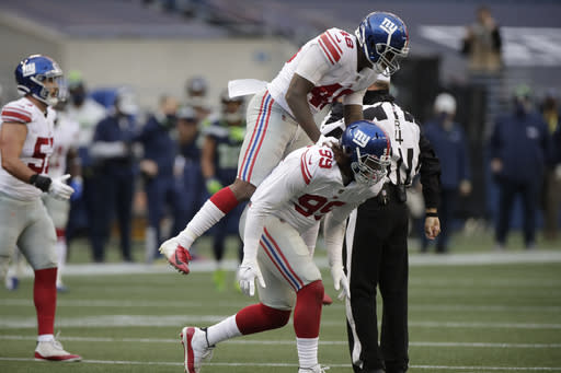 New York Giants defensive end Leonard Williams (99) celebrates with linebacker Tae Crowder (48) after Williams sacked Seattle Seahawks quarterback Russell Wilson (not shown) during the second half of an NFL football game, Sunday, Dec. 6, 2020, in Seattle. (AP Photo/Larry Maurer)