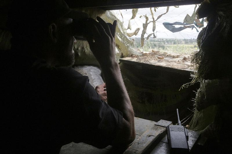 A Ukrainian serviceman looks through binoculars inside a fortified position near the front line with the pro-Russian seperatists in the village of Shyrokyne, Donetsk region, on June 29, 2015 (AFP Photo/Anatolii Stepanov)