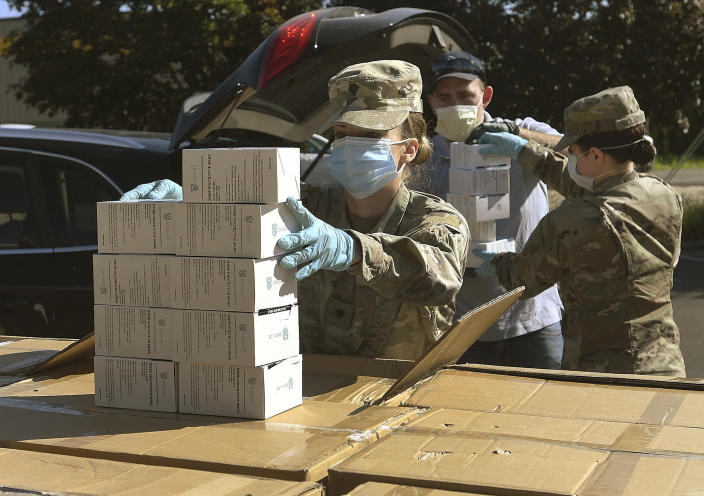 "FILE - In this Wednesday, May 27, 2020, file photo, Oregon National Guard's Ashley Smallwood, of Springfield, Ore., counts out boxes of face masks to be given to Willamette Valley farmers while participating in a distribution event at the Oregon State University Extension Service-Linn County office in Tangent, Ore. Oregon adopted a controversial rule on Tuesday, May 4, 2021 that indefinitely extends coronavirus mask and social distancing requirements in all businesses in the state. State officials say the rule, which garnered thousands of public comments, will be in place until it is ""no longer necessary to address the effects of the pandemic in the workplace."" (Mark Ylen/Albany Democrat-Herald via AP, file)"