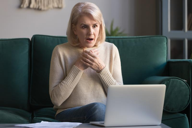 Shocked grey haired mature woman with wide opened eyes reading unexpected online news on laptop, sitting on couch, looking at screen, stressed middle aged female receiving bad email, computer problem