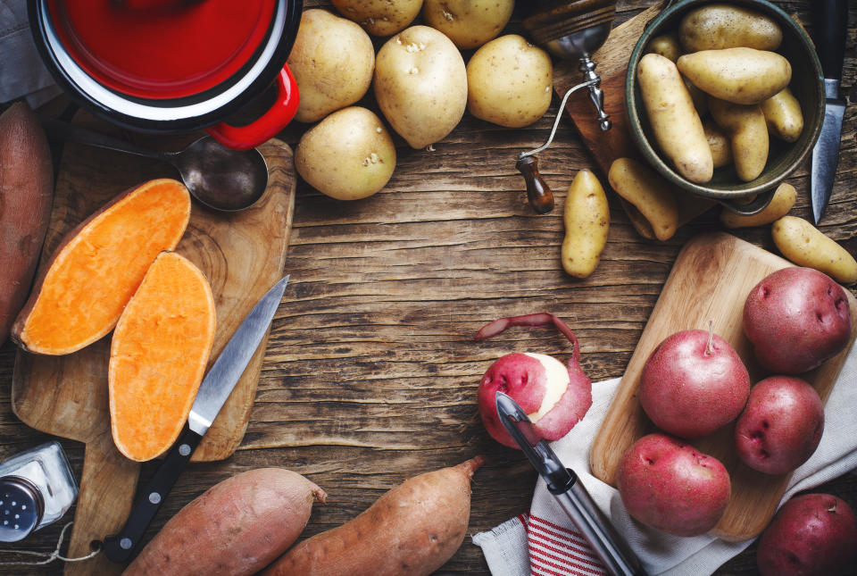 Variety of raw uncooked organic potatoes: red, white, sweet  and fingers potatoes over wooden background. Top view, copy space