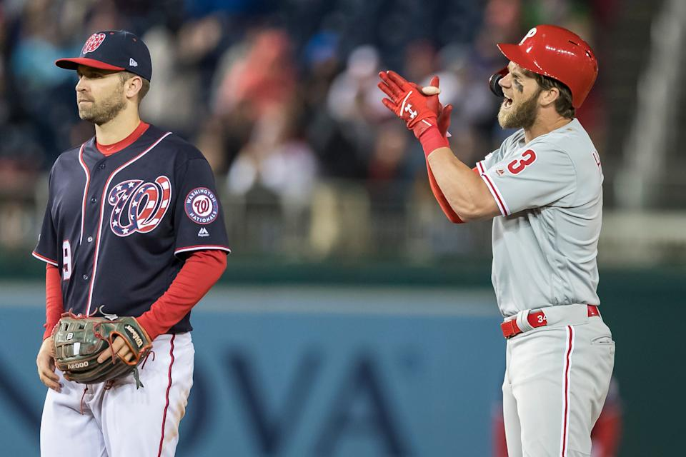 WASHINGTON, DC - APRIL 02: Bryce Harper #3 of the Philadelphia Phillies celebrates in front of Brian Dozier #9 of the Washington Nationals after hitting an RBI single during the sixth inning at Nationals Park on April 2, 2019 in Washington, DC.  (Photo by Scott Taetsch/Getty Images)