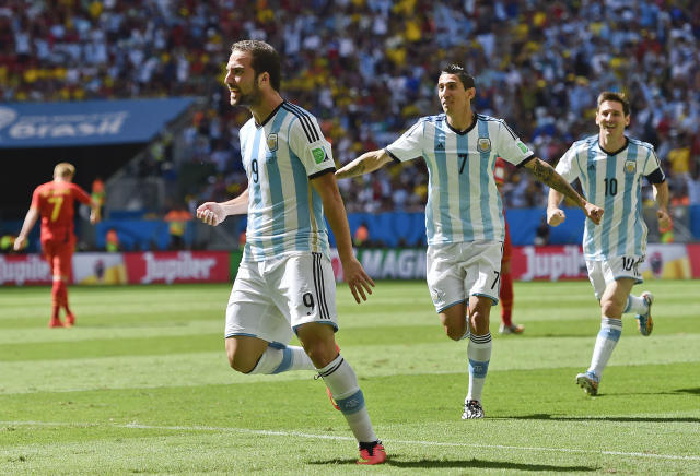 Argentina's Gonzalo Higuain, left, celebrates with Angel di Maria and Lionel Messi, right, after scoring the opening goal during the World Cup quarterfinal soccer match between Argentina and Belgium at the Estadio Nacional in Brasilia, Brazil, Saturday, July 5, 2014. (AP Photo/Martin Meissner)