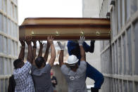 FILE - In this April 13, 2021 file photo, the remains of a woman who died from complications related to COVID-19 are placed into a niche by cemetery workers and relatives at the Inahuma cemetery in Rio de Janeiro, Brazil. As Brazil hurtles toward an official COVID-19 death toll of 500,000, epidemiologists at the University of Sao Paulo say the true toll is closer to 600,000, maybe 800,000. (AP Photo/Silvia Izquierdo, File)